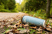 Old disposable coffee cup in the forest next to the road.