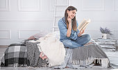 Young beautiful woman reading a book on the bed.