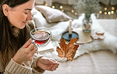 Cozy autumn home woman with a Cup of tea in her hands .