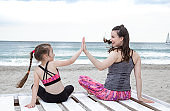 Young mother and daughter play sports on the beach.