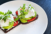Sandwich with poached eggs on a white plate.