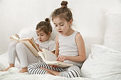Two cute little sister girls are reading a book on the bed in the bedroom.