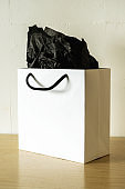 White paper gift bag with a black rope handles on wooden table.