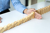 young business people use the hand to Stop wooden brick