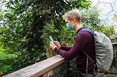 Young man wearing face mask, filming video or taking photo on phone while walking in an exotic park on holidays during coronavirus pandemic. New normal. Tourist with a backpack has trip on vacation.