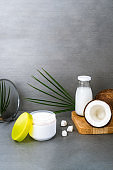 Open spa cream for body skincare and hair with coconut oil, fresh coconuts, palm leaf and bottle with coconut butter on dark gray background. Natural cosmetics concept. Vertical card. Copy space