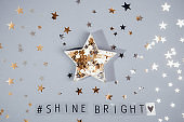 Top view hashtag Shine bright phrase and star shape full of glittering stars confetti on the grey background with shining stars. Everyday Inspirational quotes concept. Be unique. Selective focus.