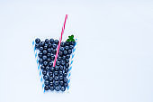 Creative layout of blueberry smoothie glass made with cocktail straws on a white background decorated with mint.Healthy food, summer drinks. Minimal food concept. Flatlay. Selective focus. Copy space.