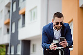 Happy young stylish businessman texting messages