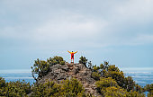 Young adult caucasian man dressed  sporty clothes with red backpack rising up hands enjoying view from Pico Ruivo mount 1861m - the highest peak on the Madeira Island,Portugal. Active vacation concept
