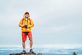 Young adult caucasian man dressed  sporty clothes with mirrorless camera on neck a enjoying view from Pico Ruivo mount 1861m - the highest peak on the Madeira Island,Portugal. Active vacation concept
