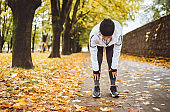 Mid aged fit athletic woman dressed modern running clothes standing and bend over to stretch the back on the footway after jogging in the autumnal city park. Active running people concept image.