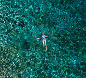 Young female floating on the back and relaxing on the warm turquoise Adriatic sea waves with rocky coastline. Carefree people vacation time concept aerial top view image.
