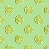 Colorful fruit pattern of fresh lime slices on green background.
