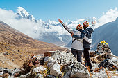 Couple rising arms rejoicing Everest Base Camp trekking route near Dughla 4620m. Backpackers left Backpacks and trekking poles and enjoying valley view with Ama Dablam 6812m peak