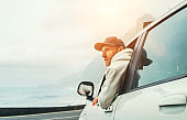 Man dressed warm hoodie and baseball cap driving his new car on the lonely road leading by the sea coast. Happy auto owner concept image.
