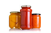 Preserved food: three glass jars on white background