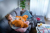 Little girl sitting on sofa with her Teddy Bear, bored at home