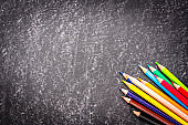 Colored pencils shot from above on blackboard background