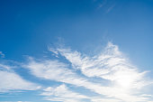 Back lit blue sky background with white clouds. Copy space