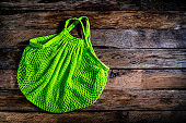Green eco friendly reusable mesh bag on rustic wooden table. Copy space