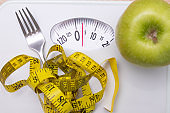 scale with measuring tape and fork with apple, diet concept
