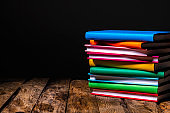 Multicolored books on rustic table against white background. Copy space