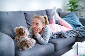Little girl laying down on sofa with her Teddy Bear, bored at home