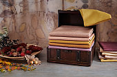 Wooden chest with stack of hand-dyed fabrics, wooden plate with autumn leaves, nuts and berries on an eco-print background