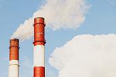 Industrial chimneys on blue sky in sunligh