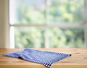 Blue checked tablecloth on wood with blur green bokeh from window kitchen background.