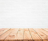 Empty wood table top with white brick wall