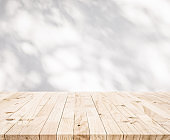 White wood table top with shadow of tree leaf on wall background