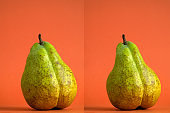 two fresh green pears in the shape of a female figure on an orange background
