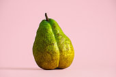 fresh green pear in the shape of a female figure on pastel pink background