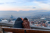 adult man and woman sitting  in  embrace on  bench on balcony of observation deck in evening against beautiful  city and sunset