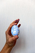 selective focus  male hand stained with blue paint holding a freshly painted Easter egg