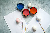 selective focus cups with dye, brushes and white eggs on a concrete background