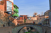 colorful houses with wooden carved balconies , old bridge and tourists