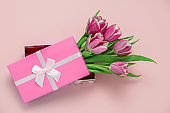 pink tulips in a box with pink satin ribbon bow on a pastel pink background