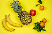 tropical fruits layout pineapple,bananas, apple and tangerines on a yellow background