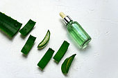 aloe vera leaves and glass jar with natural cosmetics product with aloe vera essence