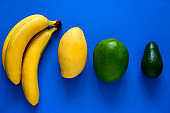 fresh bananas,mangoes and avocado on a blue background