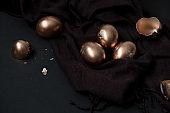 golden easter eggs and egg shells on a black background