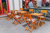 cozy wooden chairs and tables of coffee shop on a pedestrian street