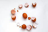 flat lay one brown egg and egg shells on a white background