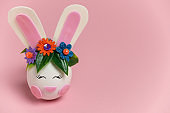 cute spring Easter card with an egg with bunny ears and a rim of spring flowers