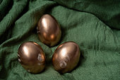golden eggs on a green textile selective focus blurred background