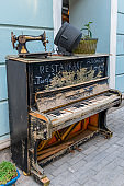 vintage broken piano and sewing machine advertising of restaurant  on a pedestrian street