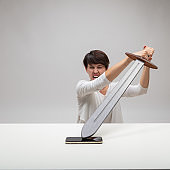 Angry woman attacking her mobile with a sword